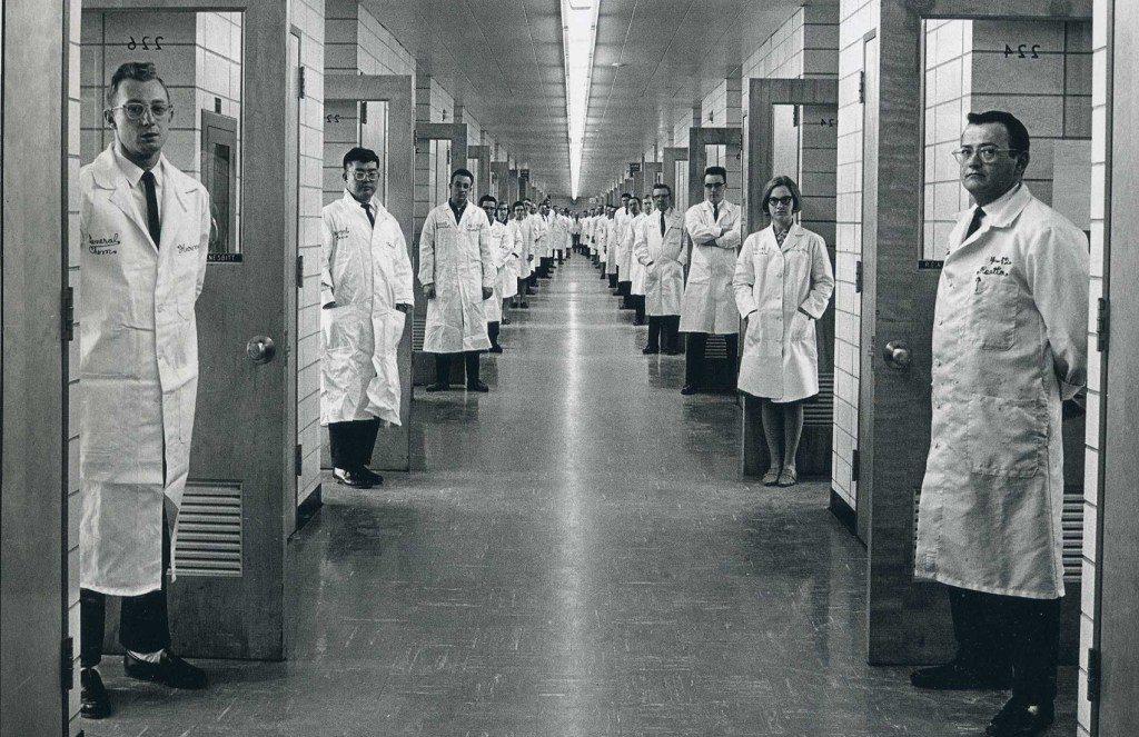 Zástup vedcov pri dverách svojich laboratórií spojených koridorom v rámci budovy Bell Labs