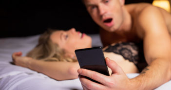surprised man looking at his phone while laying on top of woman