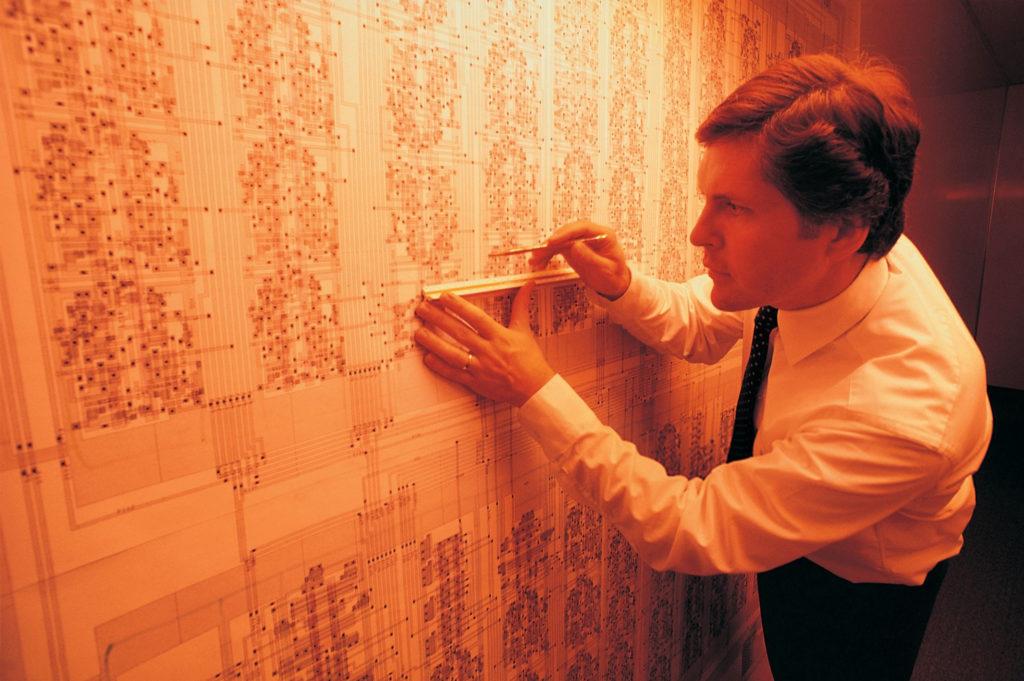 Vytváranie spojov medzi hradlami a tranzistormi s pomocou ceruzky a pravítka na obrovskej schéme pokročilého integrovaného obvodu v 80. rokoch